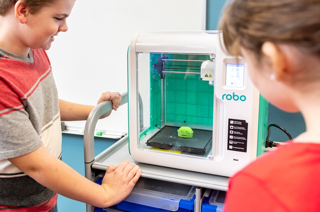 Students watch a Robo 3D printer in action.
